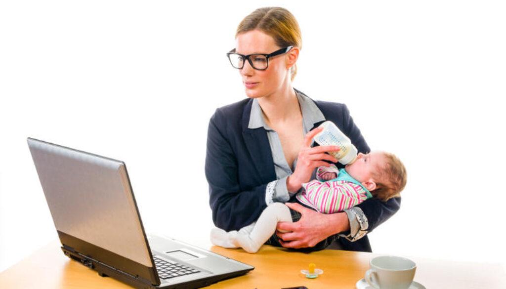 Businesswoman feeding baby